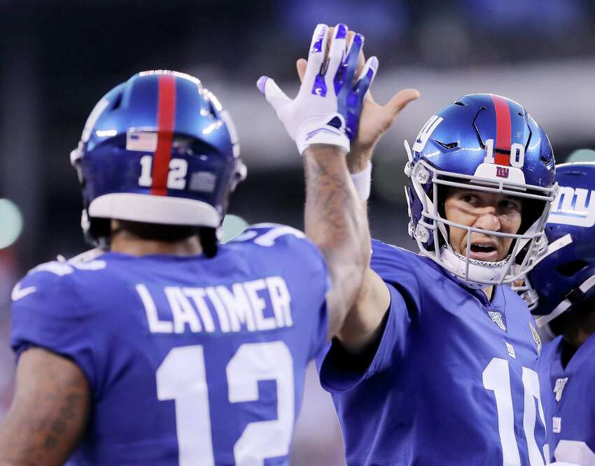 EAST RUTHERFORD, NEW JERSEY - AUGUST 16: Eli Manning #10 of the New York Giants celebrates with teammate Cody Latimer #12 after teammate Bennie Fowler III ran the ball in for a touchdown in the first quarter against the Chicago Bears during a preseason game at MetLife Stadium on August 16, 2019 in East Rutherford, New Jersey. (Photo by Elsa/Getty Images)