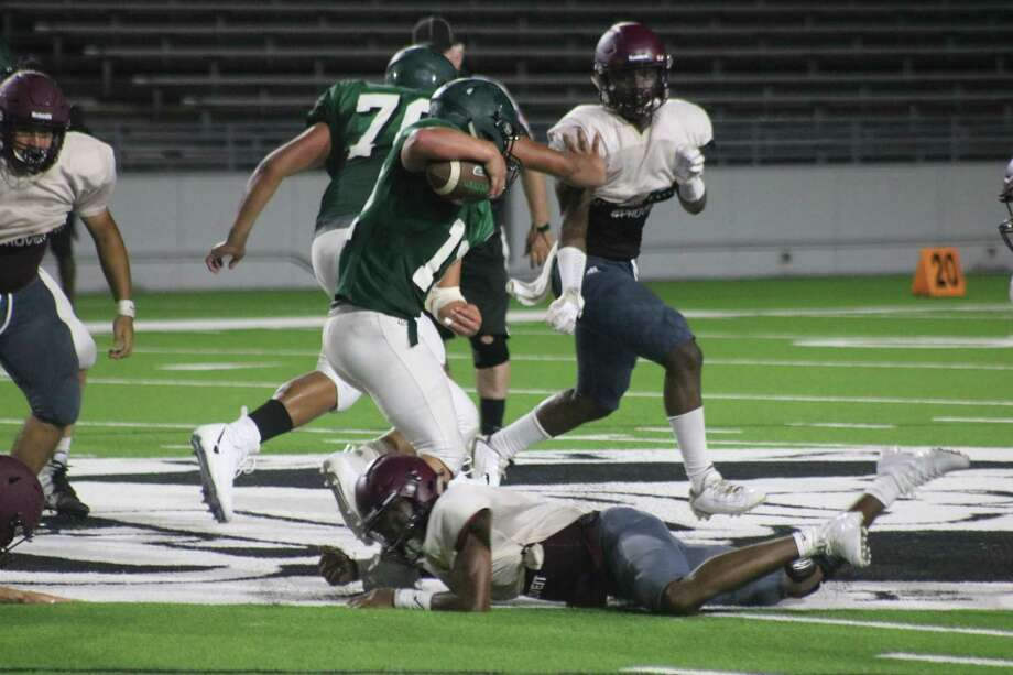 A Pasadena ballcarrier sidesteps a Baytown Lee defender on the turf during the live quarter in Friday night's scrimmage at Veterans Memorial Stadium. Photo: Robert Avery