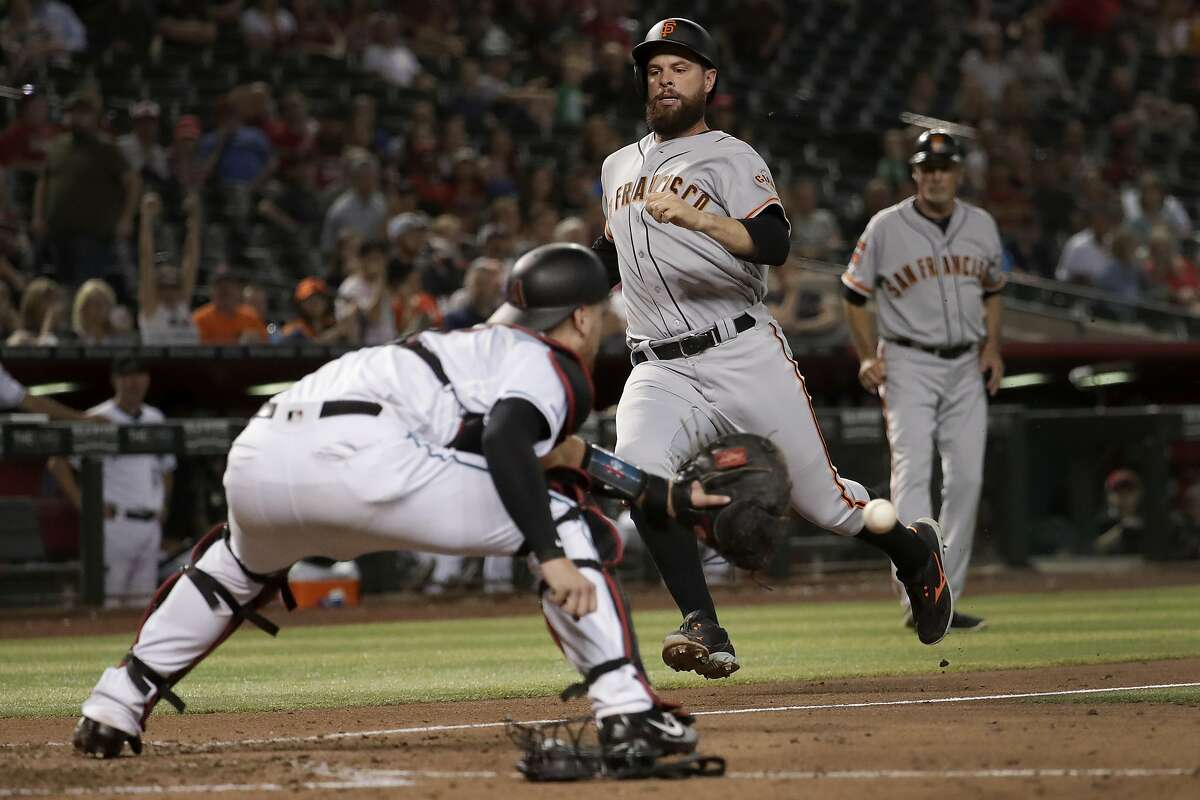 Arizona Diamondbacks catcher Carson Kelly makes the catch to tag San Francisco Giants' Brandon Belt out at the plate on a double by Donovan Solano during the eighth inning of a baseball game Friday, Aug. 16, 2019, in Phoenix. (AP Photo/Matt York)