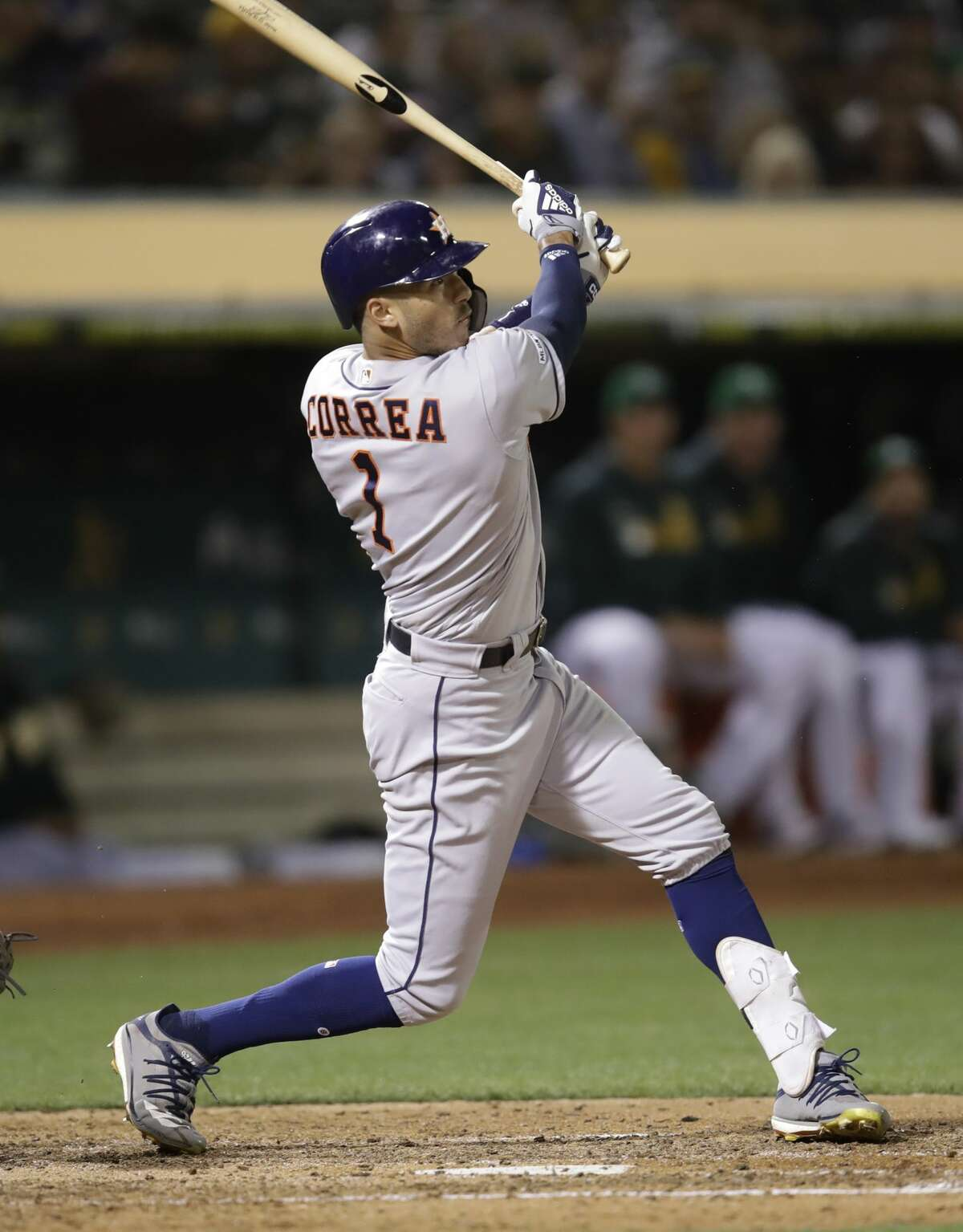 Houston Astros' Carlos Correa follows through on an RBI sacrifice fly off Oakland Athletics' Tanner Roark during the sixth inning of a baseball game Friday, Aug. 16, 2019, in Oakland, Calif. (AP Photo/Ben Margot)