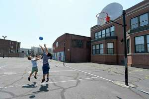 Alex Hernandez and his step brother Gabriel Torres play ball on the courts at Lathon Wilder Community Center in Stamford, Conn. on July 19, 2019. Full Court Peace, a nonprofit, started a basketball league in the South End to help bridge communities about two years ago. Now they want to revitalize the outdoor basketball courts at the community center. ShyQuinn Dix, a Stamford native, is hoping to push the initiative further and help the community and get further help from developers in the area.