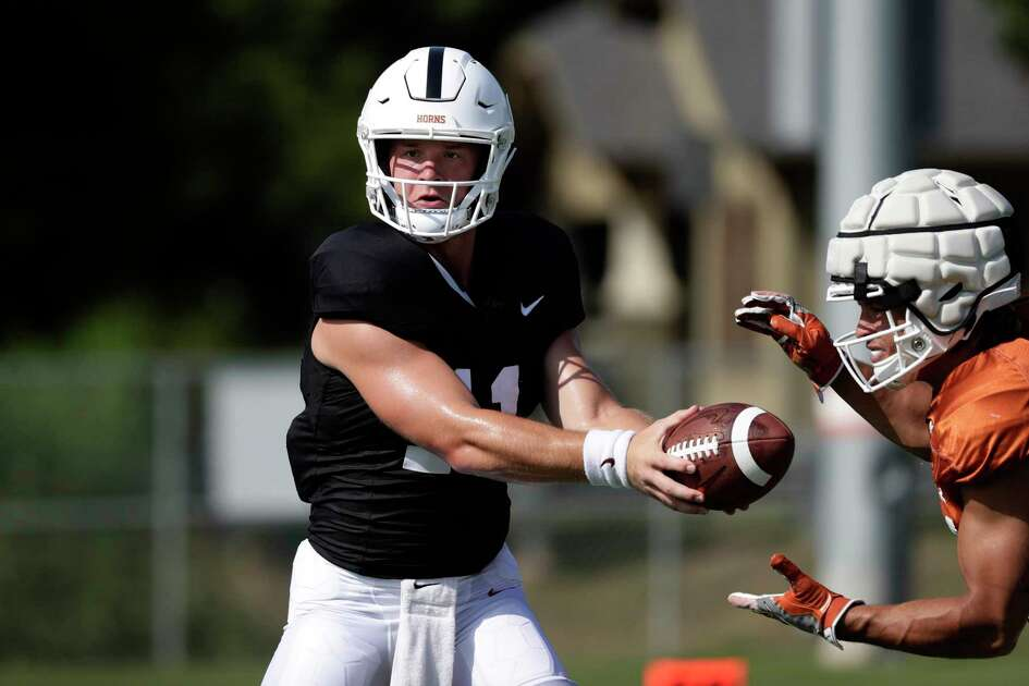 Texas quarterback Sam Ehlinger, left, and running back Jordan Whittington, right, take part in a morning practice at the team's facility in Austin, Texas, Wednesday, Aug. 7, 2019. (AP Photo/Eric Gay)
