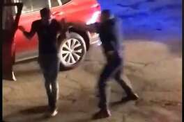 This screenshot of the Facebook video shows the moment just before the officer hits the suspect in the back of the head with the gun.