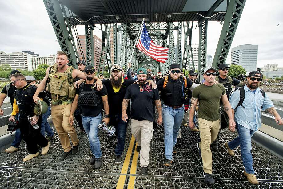 Members of the Proud Boys and other right-wing groups demonstrate in Portland. The chairman of the Proud Boys, Enrique Tarrio, walks at the front, holding a megaphone. Photo: Noah Berger / Associated Press