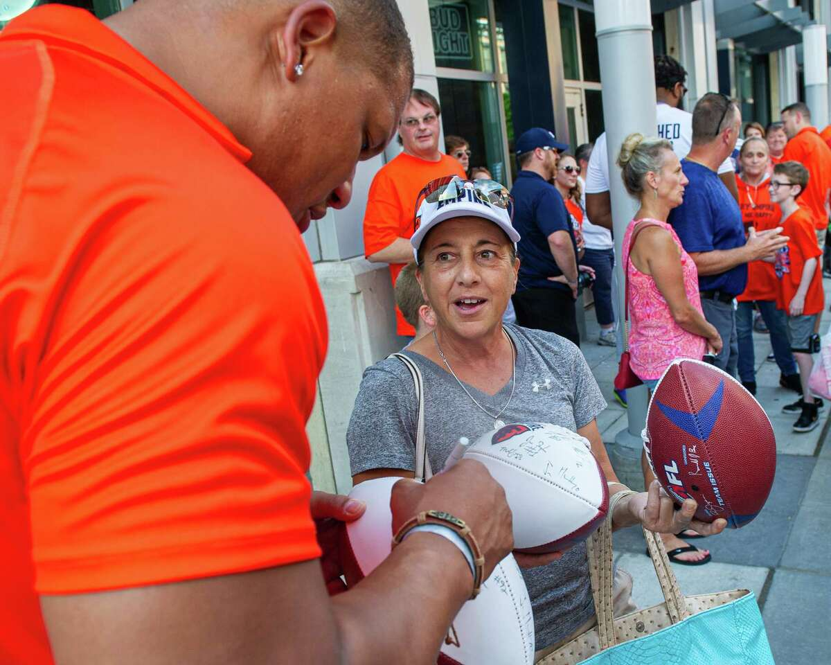 Albany lineman Brandon Sesay signs an autograph for Colton Cramer, of Schenectady at a block party to celebrate the team's Arena Bowl win in 2019. Now Sesay is with the new Empire and is set to make his debut in the National Arena League playoffs.