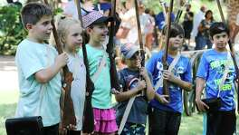 "Several children seemingly relish the role of Alamo defenders during a demonstration as the Alamo celebrates Davy Crockett's birthday with frontier demonstrations on the grounds, rubber-band rifle shooting and living historians that include a portrayal of Crockett himself on Saturday, Aug. 17, 2019. Activities started in the morning and went into the evening with a discussion about Crockett and then a showing of ""Davy Crockett: King of the Wild Frontier"" at 8 p.m. outdoors in the Alamo Gardens. (Kin Man Hui/San Antonio Express-News)"