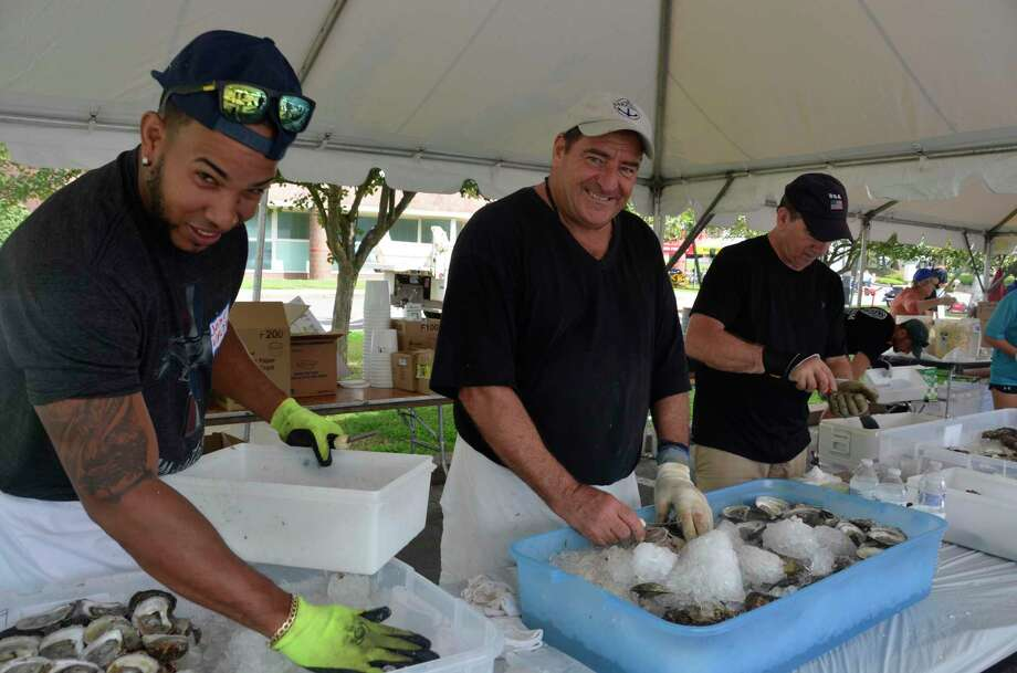 Volunteers, from left to right, Jose Valdez, Peter DeRosa and Chip Giorgi, shuck oysters at the Annual Milford Oyster Festival Saturday, Aug. 17, 2019. Photo: Jill Dion / Hearst Connecticut Media