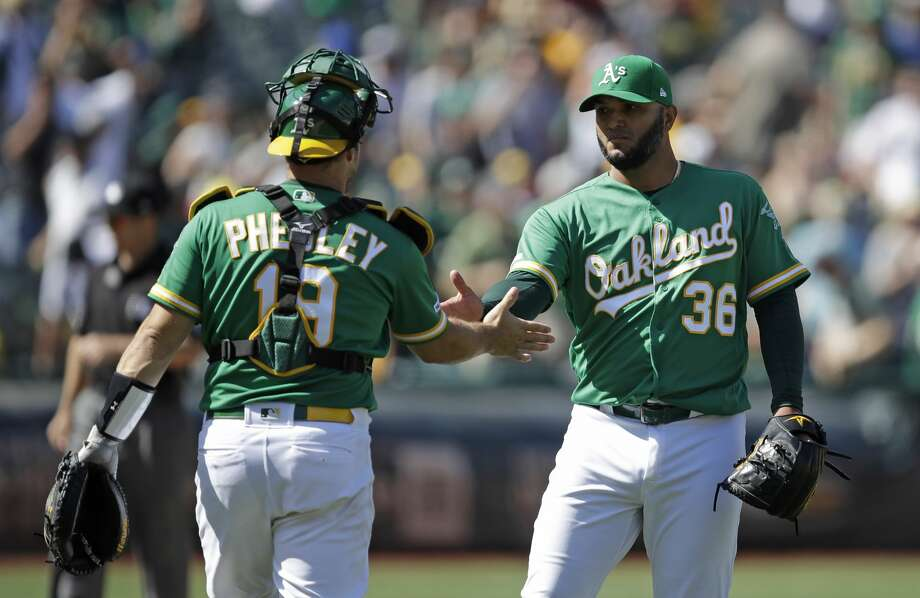 Oakland Athletics pitcher Yusmeiro Petit, right, celebrates the team's 8-4 win over the Houston Astros with catcher Josh Phegley at the end of a baseball game Saturday, Aug. 17, 2019, in Oakland, Calif. (AP Photo/Ben Margot) Photo: Ben Margot/Associated Press