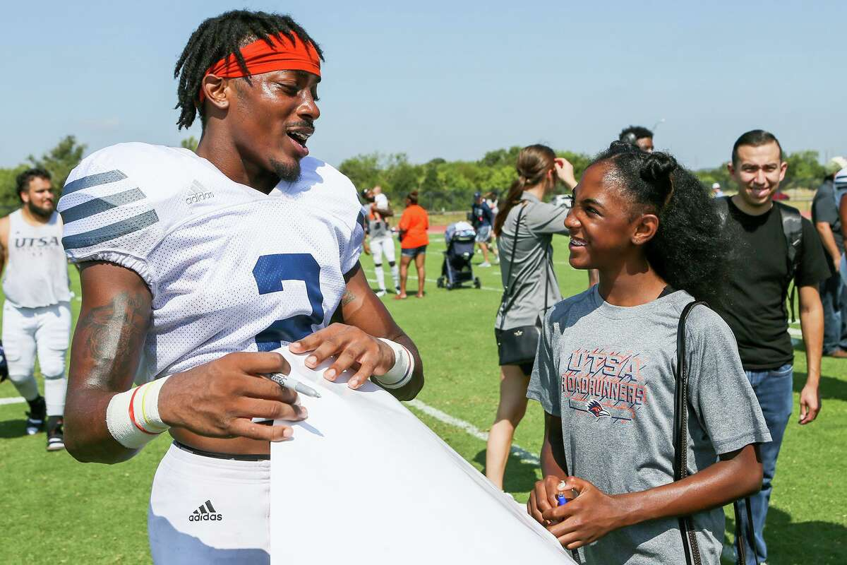 UTSA wide receiver Sheldon Jones prepares to autograph a poster for Chikere Nwachuku, 12, at the conclusion of a UTSA football practice and scrimmage in the inaugural 'Runners at the Park event at the UTSA Park West Athletic Complex on Saturday, Aug. 17, 2019.