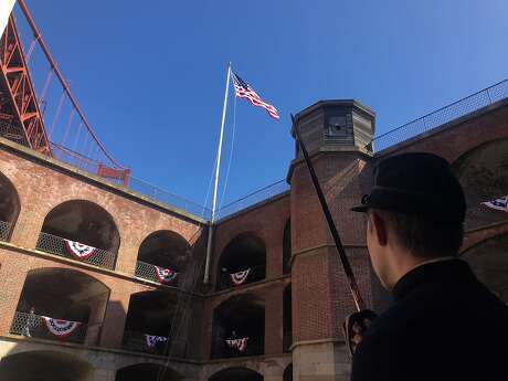 Dozens of men dressed as Union infantryman and artillerymen raise swords at San Francisco's Fort Point and watch as the American�flag is raised as part of the�annual reenactment commemorating the American Civil War era on Saturday, August 17, 2019.