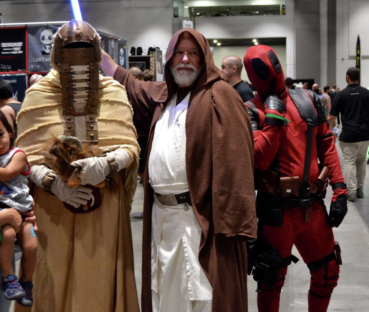 Deadpool photobombs a Tuscan Raider and Obi-Wan Kenobi at the Silicon Valley Comic Con in San Jose, California on Saturday, August 17, 2019.