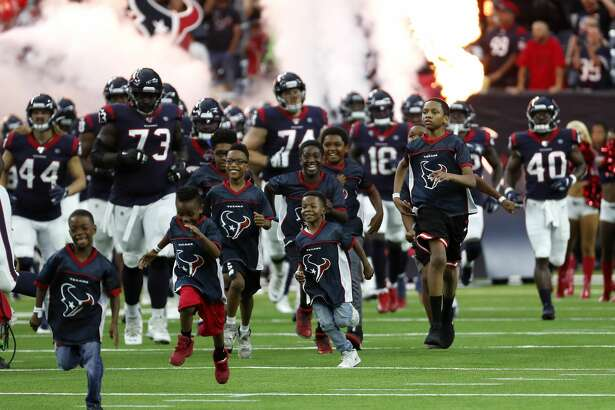 The Houston Texans are led onto the field by a group of youngsters before an NFL preseason football game against the Detroit Lions at NRG Stadium on Saturday, Aug. 17, 2019, in Houston.