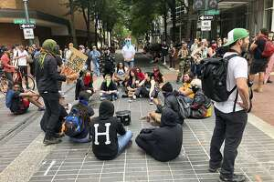 "Anti-fascist counter-demonstrators sit down in Portland, Ore., Saturday, Aug. 17, 2019. Not all who gathered Saturday were with right-wing groups or antifa. Authorities closed bridges and streets to try to keep the rival groups apart. The city's mayor said the situation was ""potentially dangerous and volatile,"" and President Donald Trump tweeted ""Portland is being watched very closely."" As of early afternoon, most of the right-wing groups had left the area via a downtown bridge. (AP Photo/Gillian Flaccus)"
