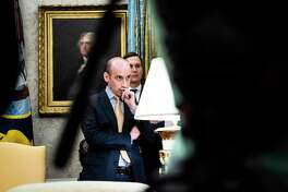 """White House advisers Stephen Miller, left, and Jared Kushner listen as President Donald Trump speaks in the Oval Office as Guatemala signs a """"safe third country"""" agreement to restrict asylum applications to the U.S. from Central America in July."""