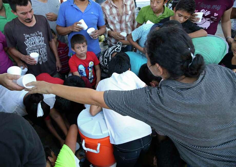 Migrantes se reúnen para recibir agua ofrecida por religiosos voluntarios en las oficinas de Inmigración de México en el Puente Internacional Número 1 en Nuevo Laredo, México, el jueves 15 de agosto de 2019. Photo: Jerry Lara /Staff Photographer / © 2019 San Antonio Express-News