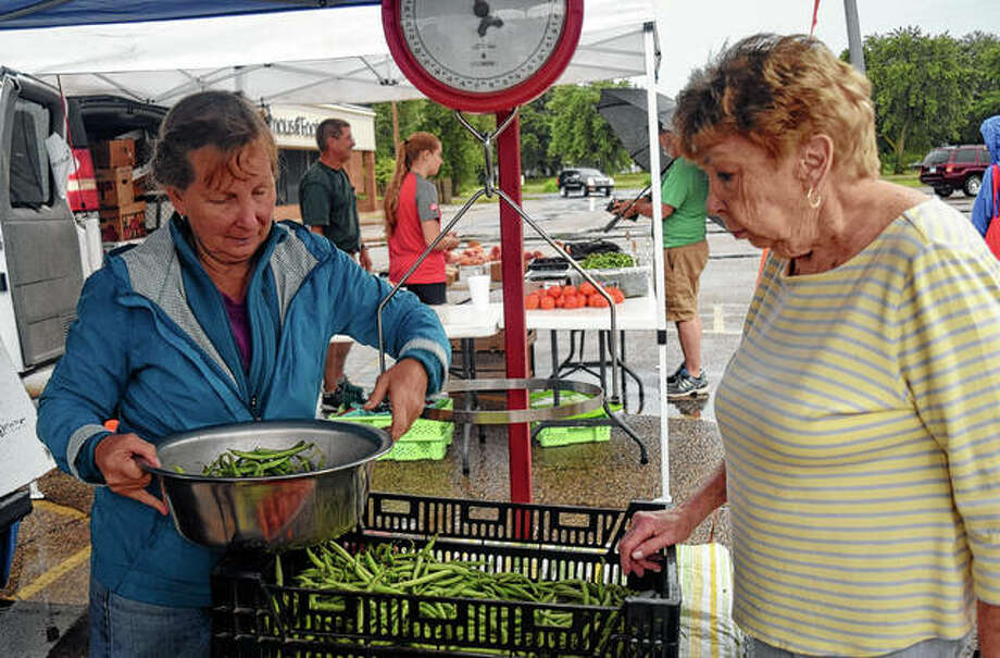 Denise Smith (left) prepares green beans for sale for Barb Dunseth Saturday at the farmer's market at Lincoln Square. Photo: Samantha McDaniel-Ogletree | Journal-Courier