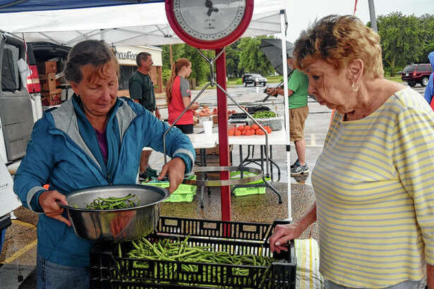 Denise Smith (left) prepares green beans for sale for Barb Dunseth Saturday at the farmer's market at Lincoln Square.