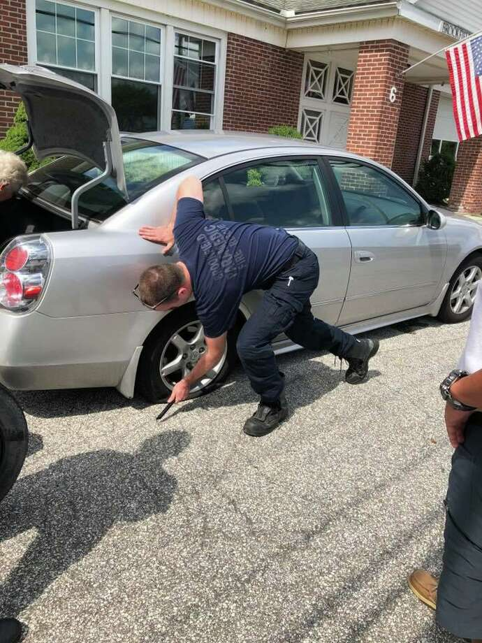 A group of first responders with Brookfield Volunteer Fire Company helped a senior citizen get back on the road when she got a flat tire on Saturday, Aug. 17, 2019. Photo: Contributed Photo/Brookfield Volunteer Fire Company Facebook / Contributed / The News-Times Contributed