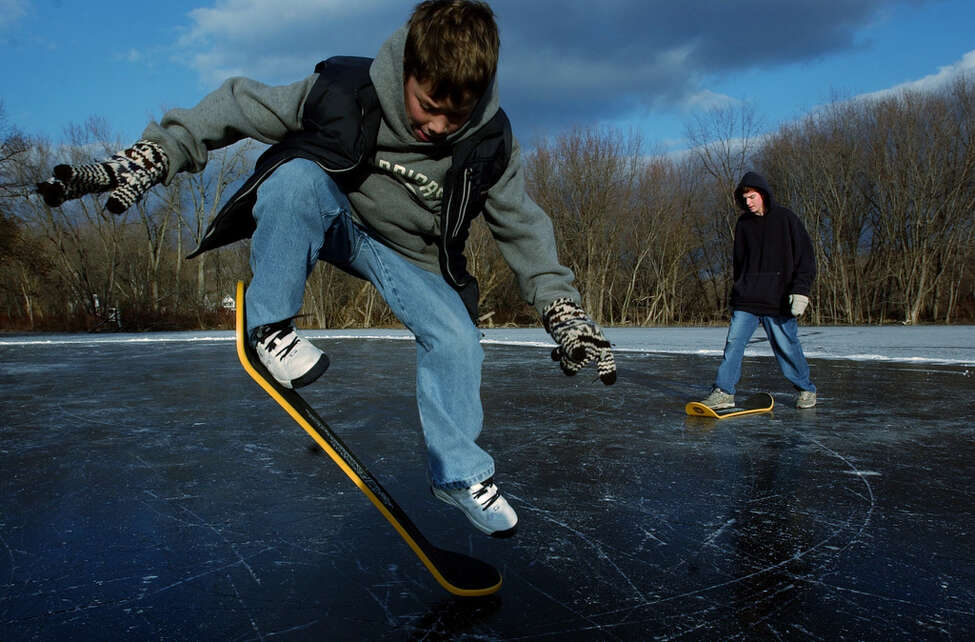 Times Union Staff Photo by Jonathan Fickies -- Daniel Patrick Ames executes a skateboard move as he and freind Owen Shaer try out their new snow skates on Ida Lake in Troy Sunday, December 30, 2001. The boys, both 13, received the snow skates as Christmas gifts. The boards resemble a skateboard deck without wheels, designed to be used on snow.