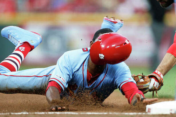 The Cardinals' Dexter Fowler is tagged out at third base trying to advance on a single off the bat of Marcell Ozuna during the fifth inning Saturday night in Cincinnati.