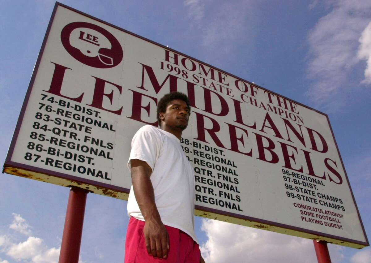 FILE PHOTO: Running Back Cedric Benson stands in front of a sign listing the recent football playoff history, including their back-to-back State titles of Midland Lee High School, Thursday, July 27, 2000.
