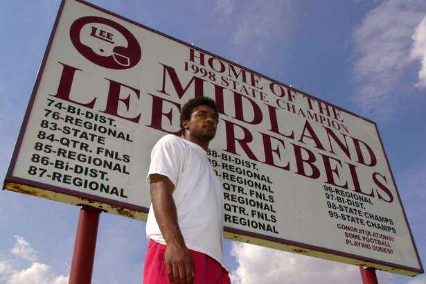 Running Back Cedric Benson stands in front of a sign listing the recent football playoff history, including their back-to-back state titles at Lee High School, Thursday, July 27, 2000.