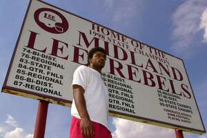 ADVANCE FOR WEEKEND, AUG. 26-27---Running Back Cedric Benson stands in front of a sign listing the recent football playoff history, including their back-to-back State titles of Midland Lee High School, Thursday, July 27, 2000.  Benson, a senior,  will be the only returning starter on the Rebels offense. (AP Photo/U. Frank Williams, Jr.) HOUCHRON CAPTION (08/30/2000):  Cedric Benson is adding a spectacular chapter to the football history of tradition-rich Midland Lee.