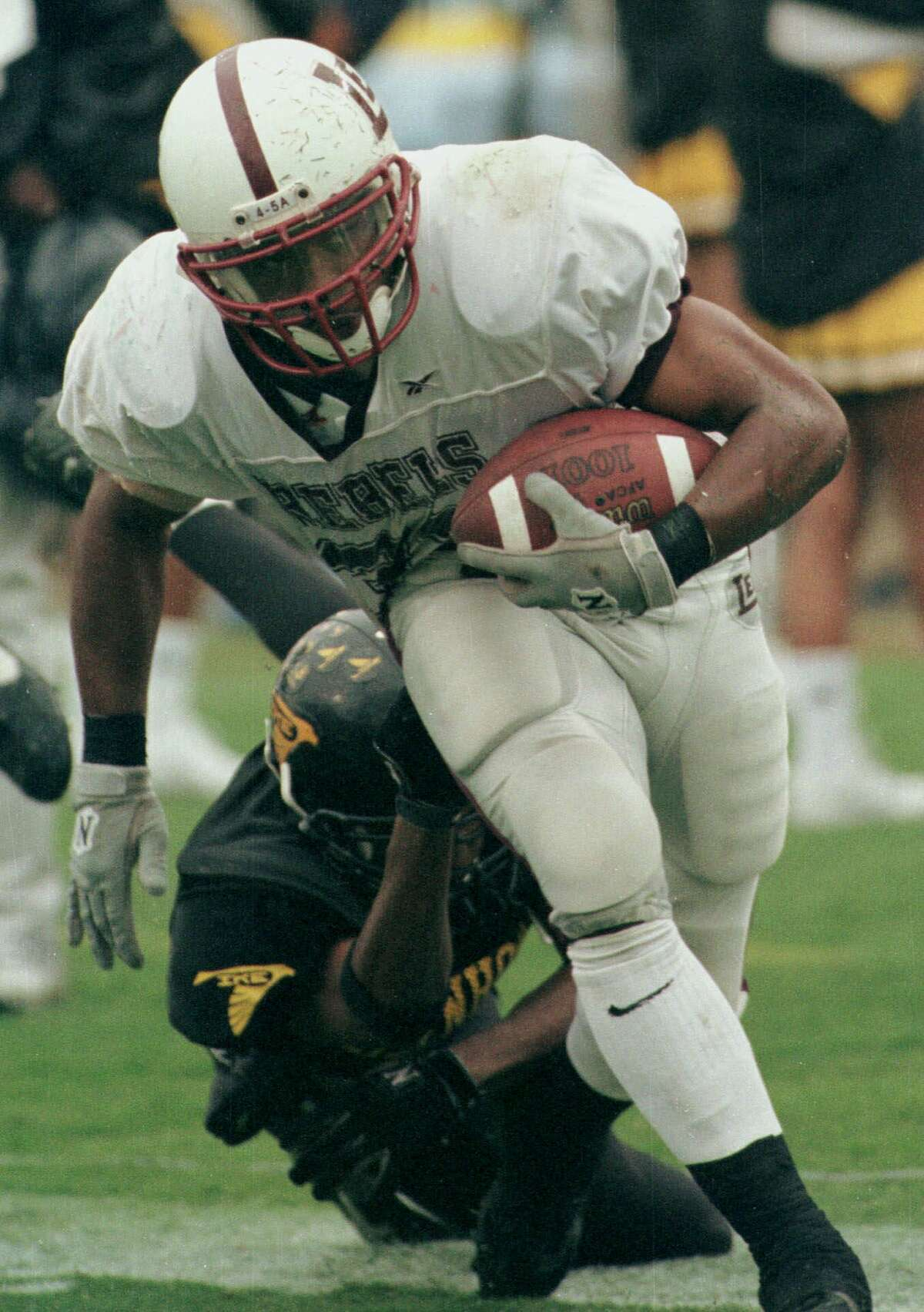 Midland Lee's Cedric Benson, tries to break the tackle of an Aldine Eisenhower defender in the Class 5A Division I UIL state football championship game Saturday, Dec. 11, 1999, in Austin, Texas. Midland won 42-21. (AP Photo/Thomas Terry) HOUCHRON CAPTION (12/10/2000): With Midland Lee running back Cedric Benson, above, one of its key catches, Texas has reeled in more than three times as many early commitments from the Chronicle's Top 100 as the next closest school.