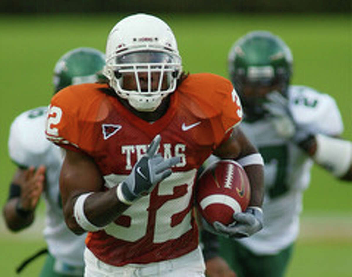 Texas running back Cedric Benson (32) outdistances a couple of North Texas defenders as he romps for a touchdown during first quarter action on Saturday, Sept. 4, 2004, in Austin, Texas.