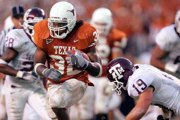 AUSTIN, TX - NOVEMBER 26: Running back Cedric Benson #32 of the University of Texas Longhorns runs the ball against safety Jaxson Appel #19 of the Texas A&M University Aggies in the fourth quarter on November 26, 2004 at Royal Memorial Stadium in Austin, Texas. (Photo by Ronald Martinez/Getty Images)