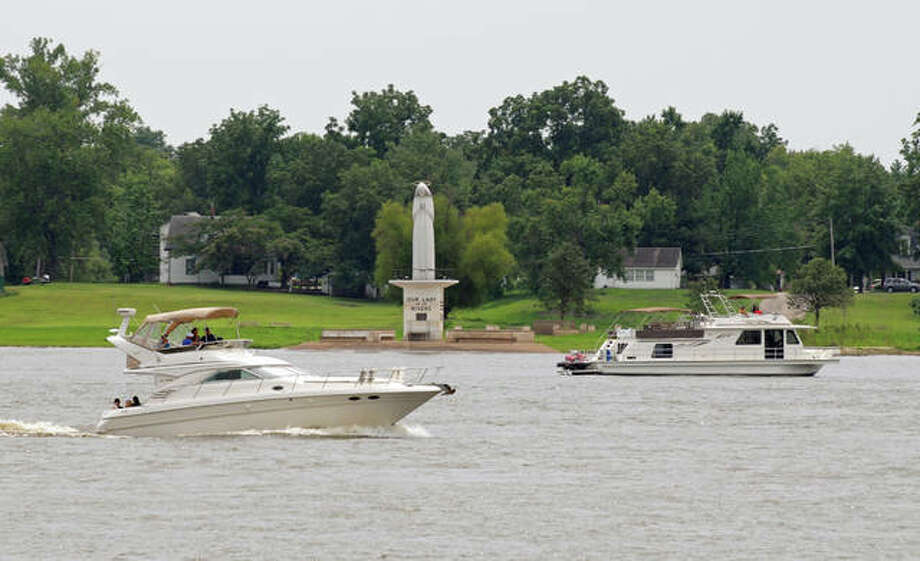 Boats on the Mississippi River pass Our Lady of the Rivers Shrine at Portage Des Sioux on Saturday during the annual Blessing of the Fleet.