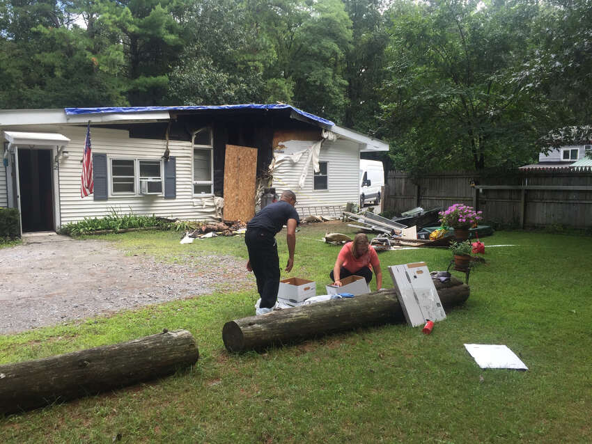 Jose and Abigail Gonzalez go through the remains of a fire that damaged the Route 50 building where they have an apartment on Sunday, August 18, 2019. The apartment shares the same building with the nonprofit Operation Adopt A Soldier. A fire the day before destroyed the building in Wilton, taking with it more than 200 care boxes that the nonprofit was about to send to U.S. troops.