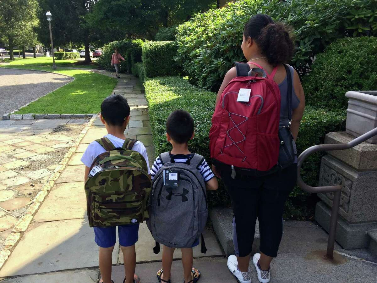 Students pick up backpacks and school supplies from Neighbor to Neighbor last week at the Tomes-Higgins House in Greenwich.