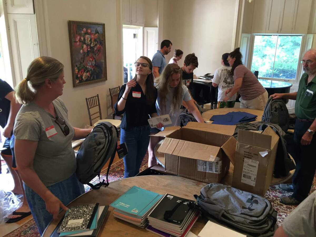 Volunteers hand out backpacks and school supplies from Neighbor to Neighbor last week at the Tomes-Higgins House in Greenwich.