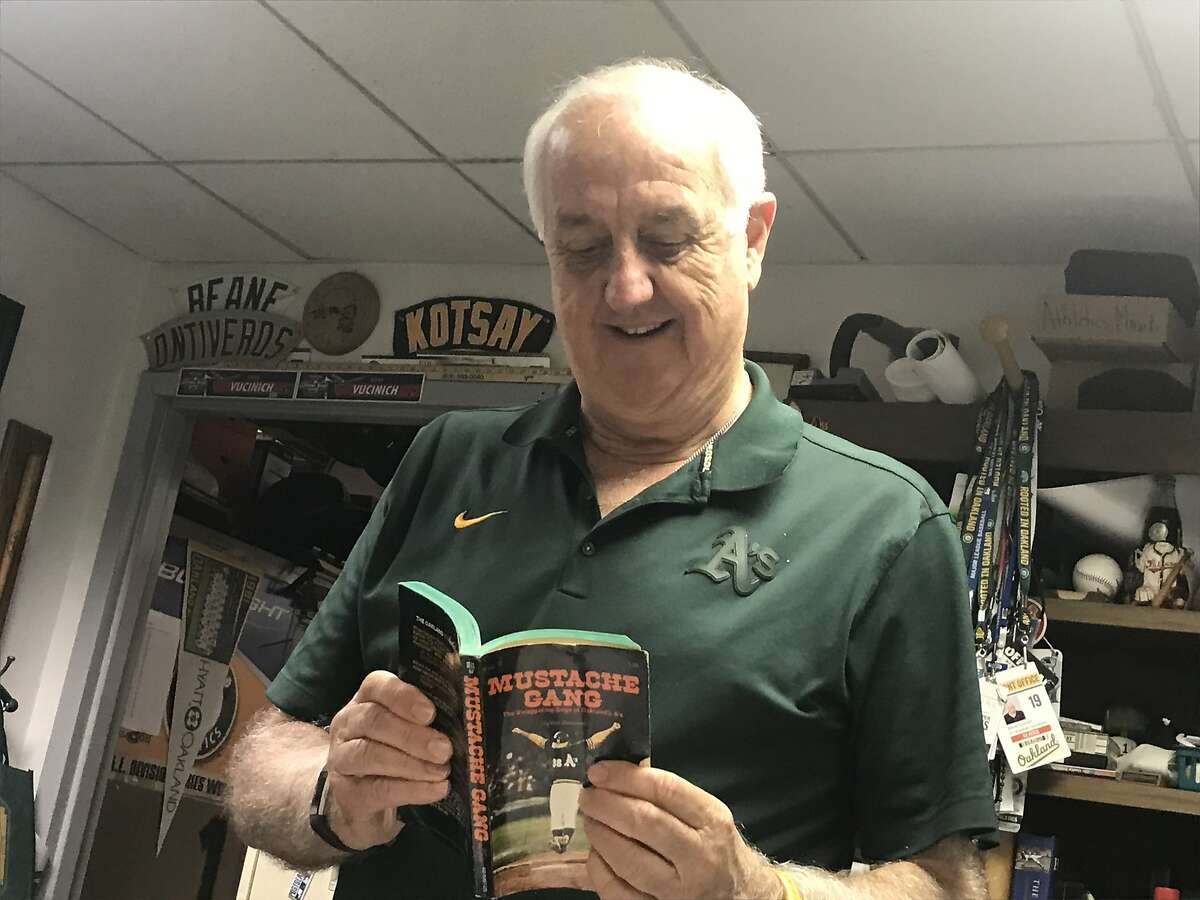"""Longtime Oakland Athletics equipment manager Steve Vucinich on August 18, 2019, with the book """"Mustache Gang,"""" written by the late Ron Bergman, an account of the A's 1972 championship season."""