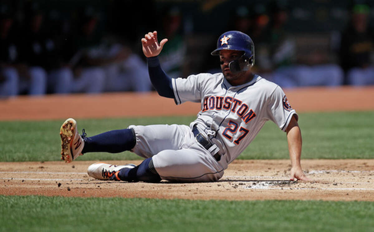 Houston Astros' Jose Altuve slides after being tagged out by Oakland Athletics catcher Josh Phegley in the first inning of a baseball game Sunday, Aug. 18, 2019, in Oakland, Calif. (AP Photo/Ben Margot)