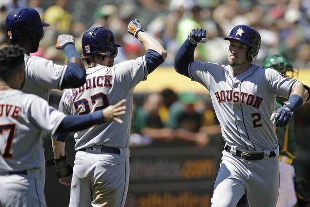 Houston Astros' Alex Bregman, right, is congratulated by Josh Reddick (22), Jose Altuve (27) and Yordan Alvarez after hitting a three run home run off Oakland Athletics' Brett Anderson in the fifth inning of a baseball game Sunday, Aug. 18, 2019, in Oakland, Calif. (AP Photo/Ben Margot)
