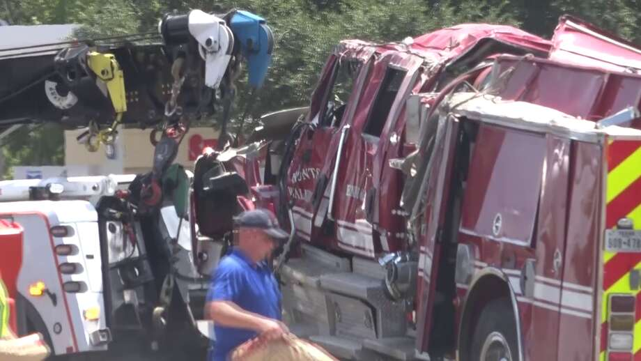 A Huntsville firefighter was critically injured Sunday after a rear-end crash caused a fire truck to roll over, leaving three firefighters trapped under the engine. Photo: Scott Engle