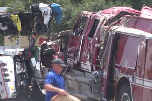 A Huntsville firefighter was critically injured Sunday after a rear-end crash caused a fire truck to roll over, leaving three firefighters trapped under the engine.