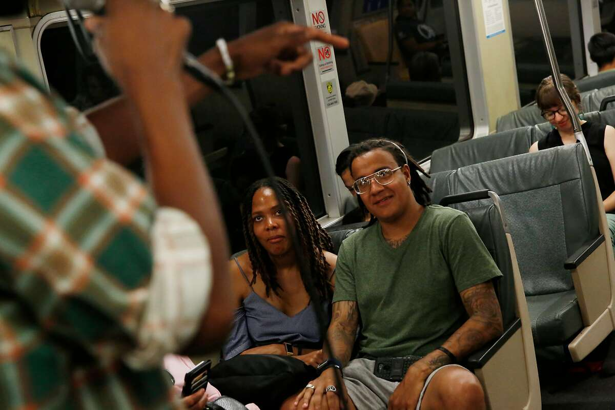 Kristin Marcus (center) of New York and Marcus Donaldson (right) of England watch as Tone Oliver (partially seen at left) performs on a BART train for passengers on Wednesday, August 14, 2019 in Oakland, Calif.