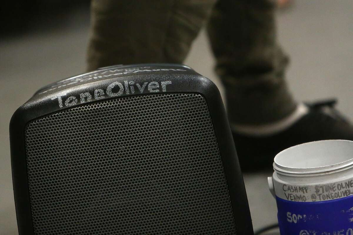 Tone Oliver's name is seen on his speaker and donation container as he performs on a BART train for passengers on Wednesday, August 14, 2019 in Oakland, Calif.