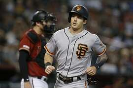 San Francisco Giants' Mike Yastrzemski scores a run after a single by Scooter Gennett in the sixth inning of a baseball game against the Arizona Diamondbacks, Sunday, Aug. 18, 2019, in Phoenix. (AP Photo/Rick Scuteri)