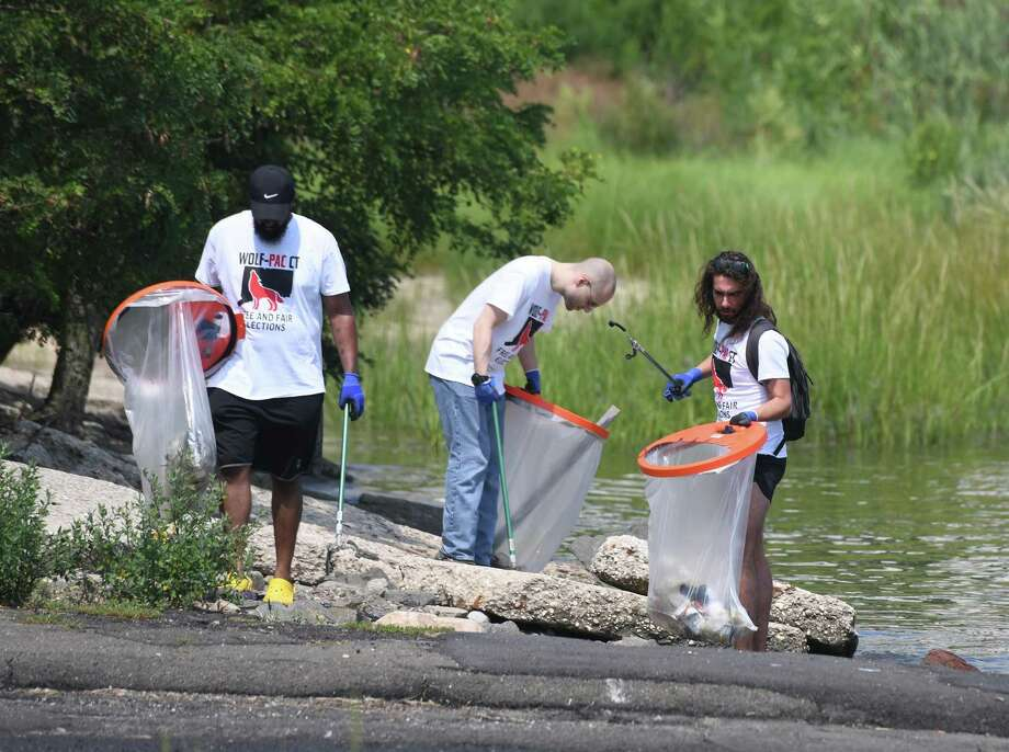 Volunteers from Wolf-PAC CT Sholom Dawit, left, David Briggs, center, and Christian Sylvia clean up trash and debris from West Beach in Stamford, Conn. Sunday, Aug. 18, 2019. State Rep. David Michel, D-Stamford, teamed up with Wolf-PAC, a group seeking to make the government more accountable for the people and end corruption, to clean the beach. Photo: Tyler Sizemore / Hearst Connecticut Media / Greenwich Time