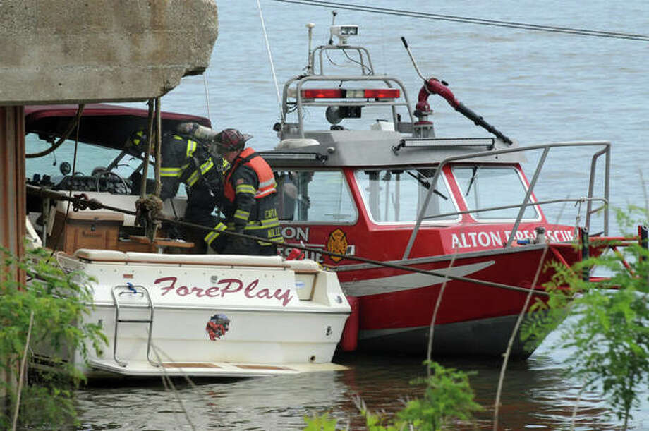 Members of the Alton Fire Department examine a boat that caught fire about 2 p.m. Saturday on the Mississippi River just north of the Ardent Mills facility. According to the department, the boat, which is owned by a Missouri man, caught fire when the inboard engine exploded. The three passengers were picked up by a passing boat and were not injured. The fire had self-extinguished by the time the fire department arrived. The boat was then towed to the Alton Marina. The department said that no fuel leaked into the river as a result of the incident.