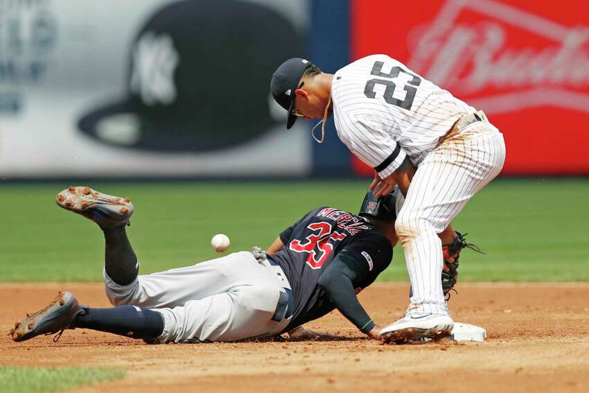 New York Yankees' second baseman Gleyber Torres (25) drops the ball as Cleveland Indians' Oscar Mercado (35) slides back to second on a pick-off attempt during the first inning of a baseball game, Sunday, Aug. 18, 2019, in New York. (AP Photo/Kathy Willens)