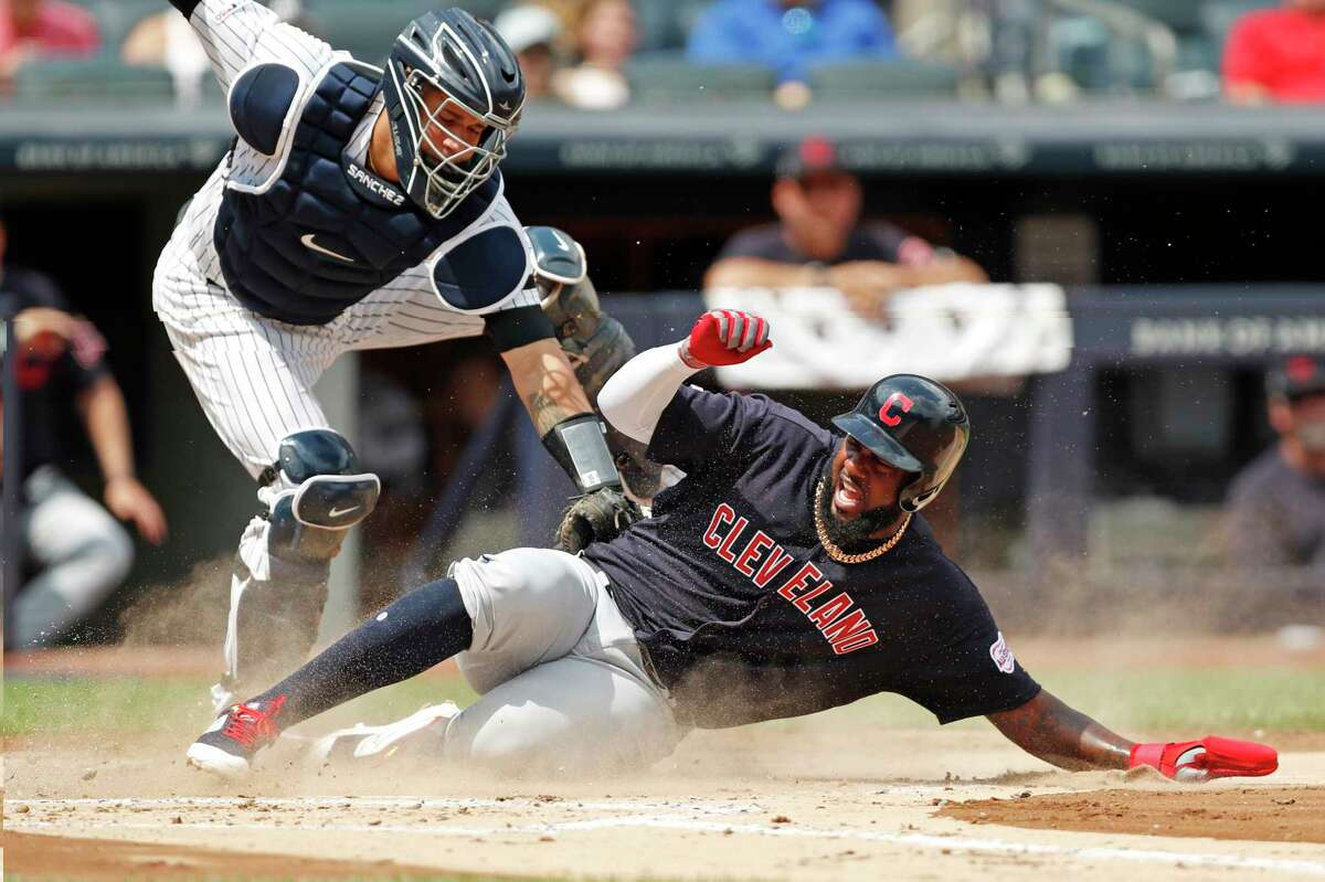 Cleveland Indians' catcher Roberto Perez, right, is safe at home as New York Yankees' catcher Gary Sanchez can't make the tag in time during the second inning of a baseball game, Sunday, Aug. 18, 2019, in New York. The play came when the Indians' Greg Allen grounded into a fielder's choice to the pitcher. (AP Photo/Kathy Willens)