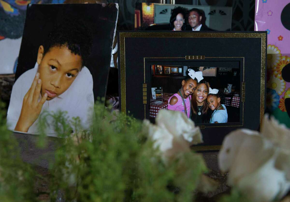 Bennie Hunter-Hooey, 55, mother of Dan Hunter, puts photographs of her deceased son on the fireplace at the house he grew up in on Friday, Aug. 16, 2019, in Houston. Hunter, 28, was shot outside a night club on August 4. The photograph on the left is a young Hunter. The photograph on the right is Hunter-Hooey with Hunter's two daughters, Aniyah, 9, and Harlei, 5.