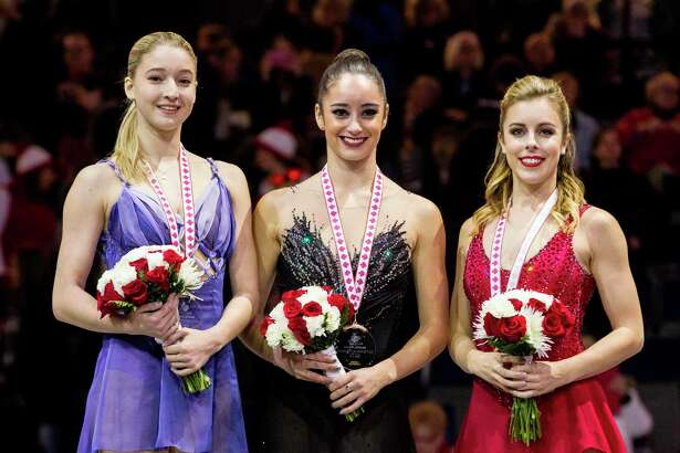 Women's competition gold medalist Kaetlyn Osmond (C) of Canada poses for photos with silver medalist Maria Sotskova of Russia (L) and bronze medalist Ashley Wagner of the United States during the medal ceremony at the 2017 Skate Canada International ISU Grand Prix event in Regina, Saskatchewan, October 28, 2017. / AFP PHOTO / Geoff RobinsGEOFF ROBINS/AFP/Getty Images