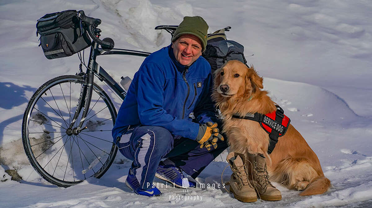 Jimmy Thomas and his service dog, Boots, appear in front of the bike Thomas rode cross country to raise funds for Woofs for Warriors. (Provided)