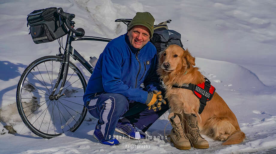 Jimmy Thomas and his service dog, Boots, appear in front of the bike Thomas rode cross country to raise funds for Woofs for Warriors. (Provided) Photo: Stephen P. Willette / All Rights Reserved 2019